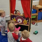 Children put on a puppet show during preschool playtime